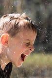 Ragazzo giovane bagnato d'inzuppamento che ride hysterically Fotografie Stock Libere da Diritti