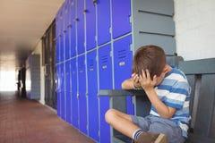 Ragazzo infelice che si siede sul banco in corridoio Fotografia Stock Libera da Diritti