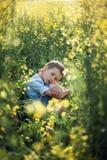 Ragazzo insoddisfatto del bambino in età prescolare che si siede nell'erba alta, nel fronte propping con le mani ed esaminante ma immagini stock libere da diritti