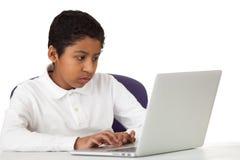 Ragazzo ispano che studia con il computer portatile Fotografia Stock Libera da Diritti