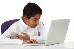 Ragazzo ispano che studia con il computer portatile su fondo bianco Immagini Stock