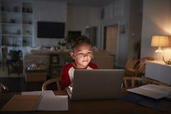 Ragazzo ispano Pre-teen che si siede al tavolo da pranzo che fa il suo compito facendo uso di un computer portatile, vista fronta fotografia stock libera da diritti