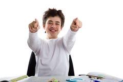 Ragazzo latino felice che indica entrambi i dito indice mentre facendo compito Fotografie Stock