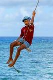 Ragazzo locale che oscilla su un'oscillazione della corda nel villaggio di Lavena su Taveuni Immagine Stock
