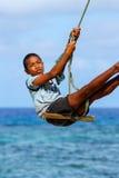 Ragazzo locale che oscilla su un'oscillazione della corda nel villaggio di Lavena su Taveuni Fotografie Stock Libere da Diritti