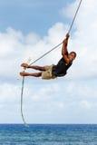 Ragazzo locale che oscilla su un'oscillazione della corda nel villaggio di Lavena su Taveuni Immagini Stock