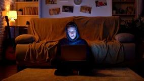 Ragazzo in maglia con cappuccio facendo uso del computer portatile per fendere i siti Web o guardare contenuto proibito immagine stock