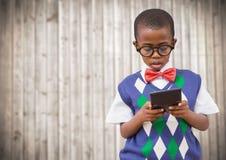 Ragazzo in maglia e cravatta a farfalla con il calcolatore contro il pannello di legno confuso Fotografie Stock Libere da Diritti