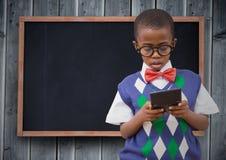 Ragazzo in maglia e cravatta a farfalla con il calcolatore contro la lavagna ed il pannello di legno grigio immagine stock libera da diritti