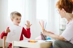 Ragazzo in maglione rosso che impara contare durante le attivit? extracurriculari immagine stock