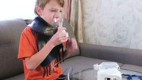 Ragazzo malato che inala attraverso la maschera dell'inalatore Utilizzi il nebulizzatore e l'inalatore per il trattamento archivi video