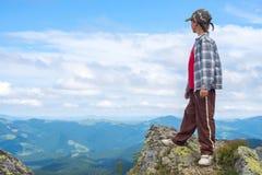 Ragazzo nel cappuccio che sta su una scogliera rocciosa nelle montagne Fotografie Stock