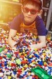 Ragazzo nel gioco di vetro con molti giocattoli Fotografie Stock Libere da Diritti