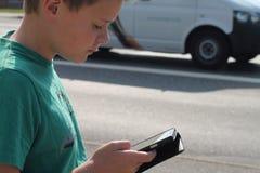 Ragazzo nel traffico che esamina telefono cellulare Fotografie Stock