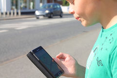 Ragazzo nel traffico che esamina telefono cellulare Fotografia Stock Libera da Diritti