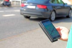 Ragazzo nel traffico che esamina telefono cellulare Fotografia Stock