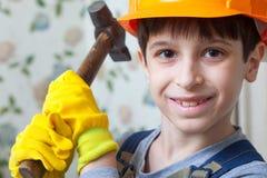 Ragazzo nell'immagine di un costruttore con un martello in sue mani Immagine Stock