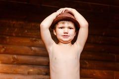 Ragazzo nudo in un cappello che giudica il suo capo immagini stock libere da diritti