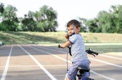 Ragazzo in occhiali da sole che guidano bicicletta fotografia stock