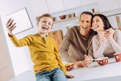 Ragazzo ottimistico che prende un selfie dei suoi genitori in cucina fotografia stock libera da diritti