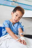 Ragazzo paziente asiatico con il dispositivo di venipunzione salino (iv). Immagini Stock