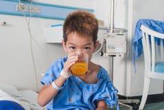 Ragazzo paziente asiatico con il dispositivo di venipunzione salino (iv) sul letto di ospedale. Fotografia Stock