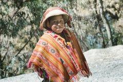 Ragazzo peruviano indigeno sorridente che porta poncio tradizionale fatto a mano variopinto e un cappello Fotografie Stock Libere da Diritti