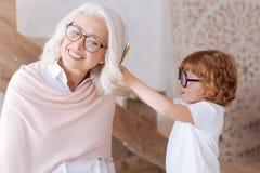 Ragazzo piacevole sveglio che mette le piume nei suoi capelli delle nonne Fotografie Stock