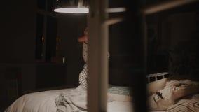 Ragazzo in pigiami che saltano sul letto nella camera da letto della sua casa Giochi di risata con un giocattolo stock footage
