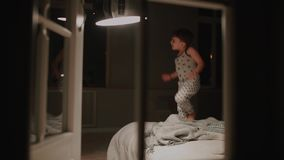 Ragazzo in pigiami che saltano sul letto nella camera da letto della sua casa Giochi di risata con un giocattolo video d archivio