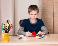 Ragazzo pre teenager che fa progetto elettronico della scuola nella sua stanza a casa Immagini Stock