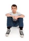 Ragazzo pre teenager che si siede in jeans e maglietta Immagini Stock Libere da Diritti