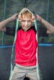 Ragazzo pre-teenager insolente che guarda attraverso la rete del trampolino Fotografia Stock Libera da Diritti