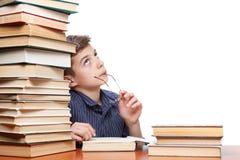Ragazzo premuroso che cerca e che sogna di una pila di libri su fondo bianco Immagini Stock