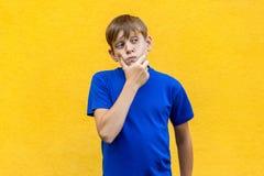 Ragazzo premuroso che distoglie lo sguardo mentre stando contro il backgr giallo fotografie stock