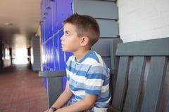 Ragazzo premuroso che si siede sul banco in corridoio Immagine Stock