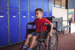 Ragazzo premuroso che si siede sulla sedia a rotelle Fotografia Stock