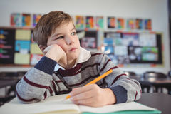 Ragazzo premuroso che studing mentre sedendosi allo scrittorio Immagini Stock