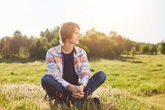 Ragazzo premuroso serio in abbigliamento casual che si siede le gambe attraversate sull'erba verde che guarda da parte con il sun Fotografie Stock
