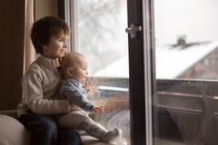 Ragazzo prescolare, tenendo suo fratello del bambino, sedentesi dalla finestra i fotografie stock