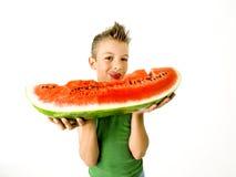 Ragazzo punk che mangia una grande fetta di anguria Fotografia Stock