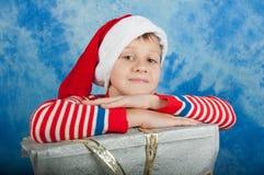 Ragazzo in Santa che hatlaying sui regali di natale Immagini Stock