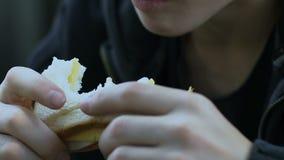 Ragazzo senza tetto affamato che mangia panino, bambino che vive fuori dalla carità, primo piano di povertà video d archivio