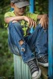 Ragazzo senza tetto sporco della foto con i jeans lacerati Fotografia Stock