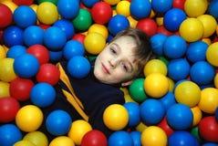 Ragazzo in sfere multi-coloured Fotografia Stock
