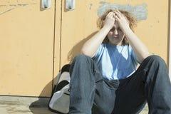 Ragazzo solo triste nel campo da giuoco della scuola Immagine Stock