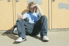 Ragazzo solo triste nel campo da giuoco della scuola Fotografia Stock