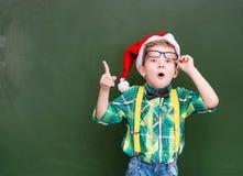 ragazzo sorpreso in cappello rosso di natale vicino ad uno showi verde della lavagna Fotografie Stock