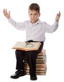 Ragazzo sorpreso che si siede sul mucchio dei libri con magnifyer Fotografia Stock Libera da Diritti
