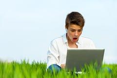 Ragazzo sorpreso con il computer portatile all'aperto. Fotografie Stock